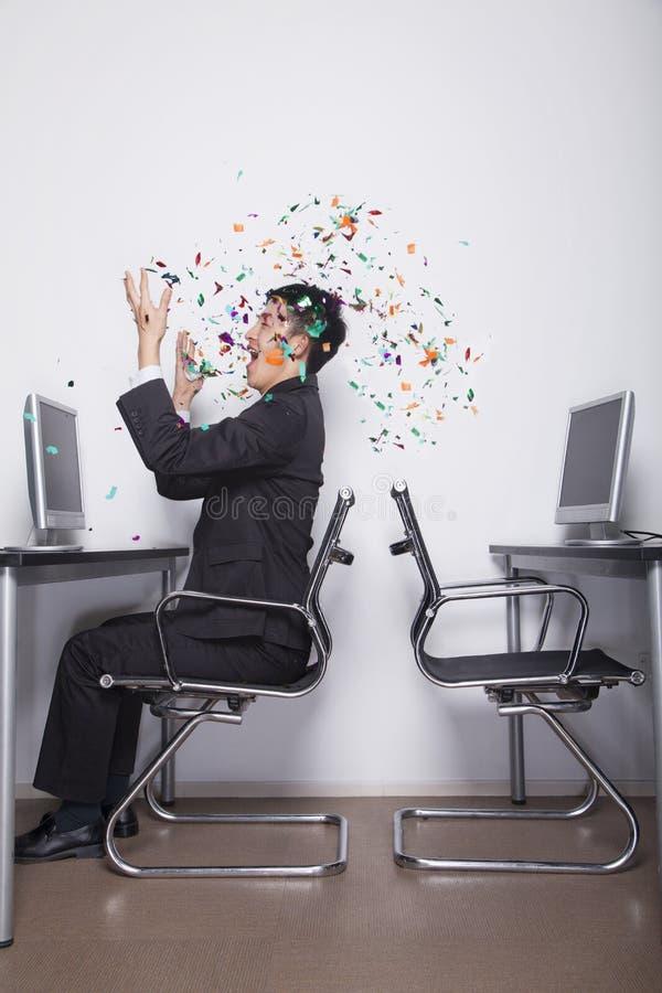 Confettis de lancement de jeune homme d'affaires dans le bureau photographie stock libre de droits