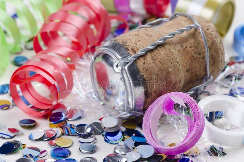 Confettis, flammes et liège de champagne sur un fond blanc photos stock