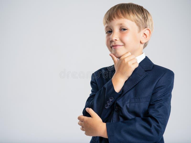 Confiado chico rubio vestido con traje formal con corbata azul Retrato de niño blanco con traje de negocios azul, posando en el e fotografía de archivo