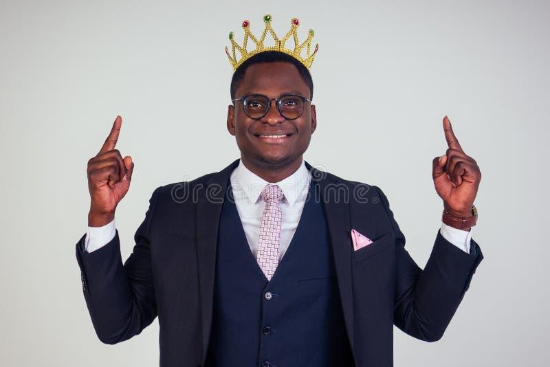 Confiado hombre de negocios rey con traje clásico negro con corbata y lentes puestos en la cabeza en blanco imagen de archivo