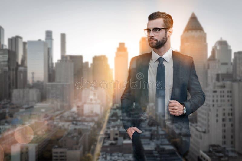Confiado y hermoso Retrato del hombre de negocios barbudo hermoso en los vidrios que miran lejos mientras que se opone a de fotos de archivo libres de regalías