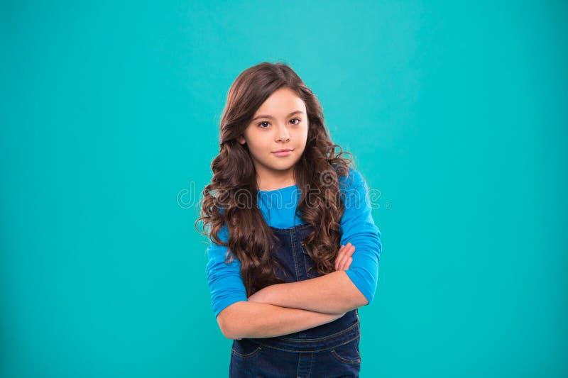 Confiança da educação Cabelo longo da menina da criança que levanta seguramente O penteado encaracolado da menina sente seguro Mã imagens de stock