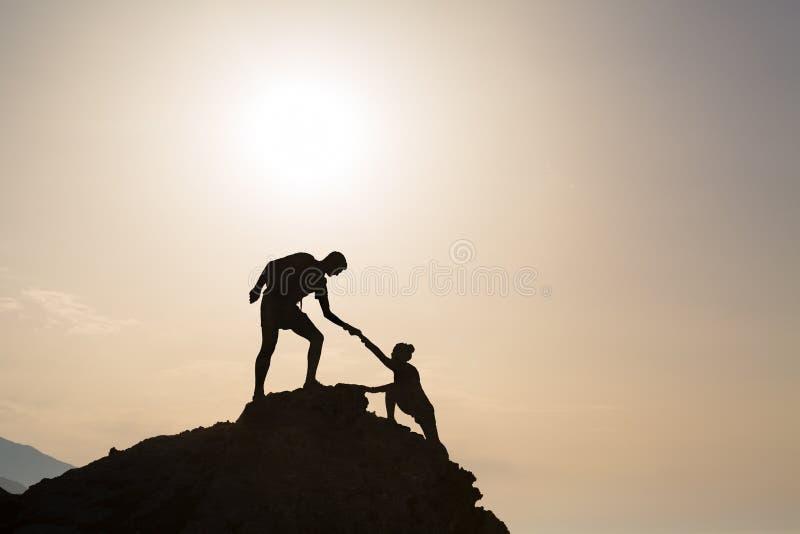 Confiança da mão amiga dos pares dos trabalhos de equipa em montanhas inspiradores imagens de stock