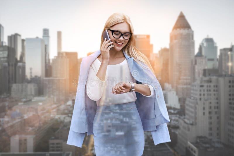 Confiança e pontualidade Retrato da senhora positiva do negócio que fala pelo telefone e que olha seu relógio ao estar fotos de stock