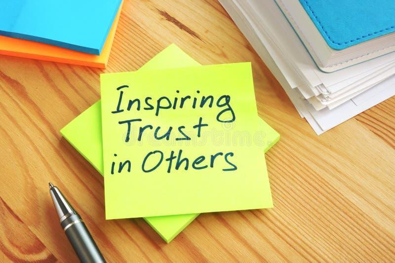 Confiance de inspiration dans d'autres écrites à la main sur une page Travail dans le concept d'équipe images stock