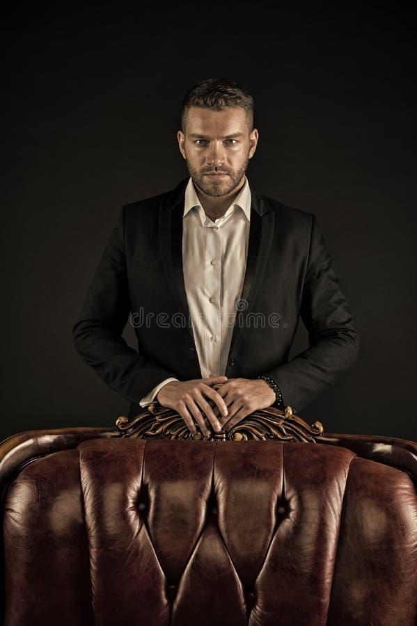 Confianza y carisma Soporte del hombre en la butaca de cuero en fondo oscuro Hombre barbudo en traje formal Hombre de negocios co fotografía de archivo