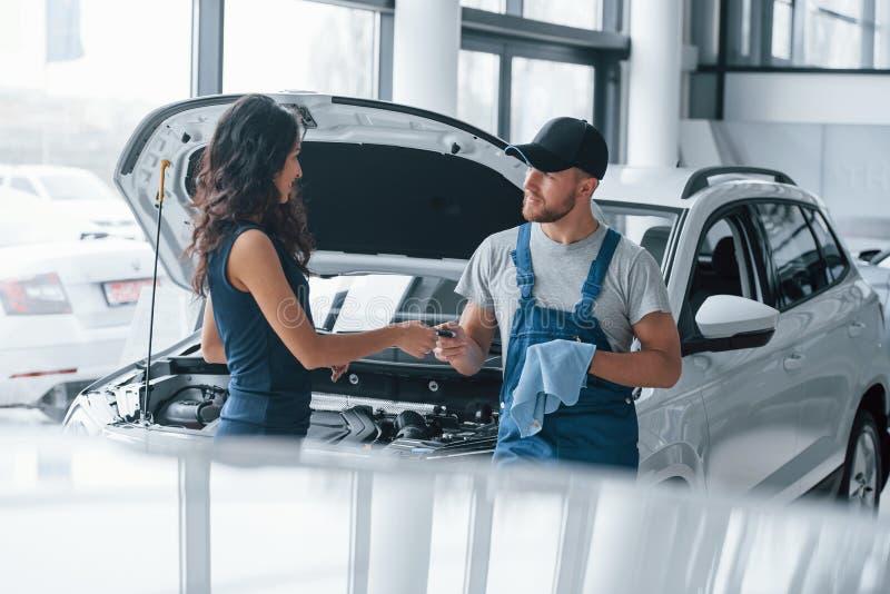 Confianza y ocupación Mujer en el salón de autos con una empleada con uniforme azul llevando su auto reparado de vuelta imagen de archivo