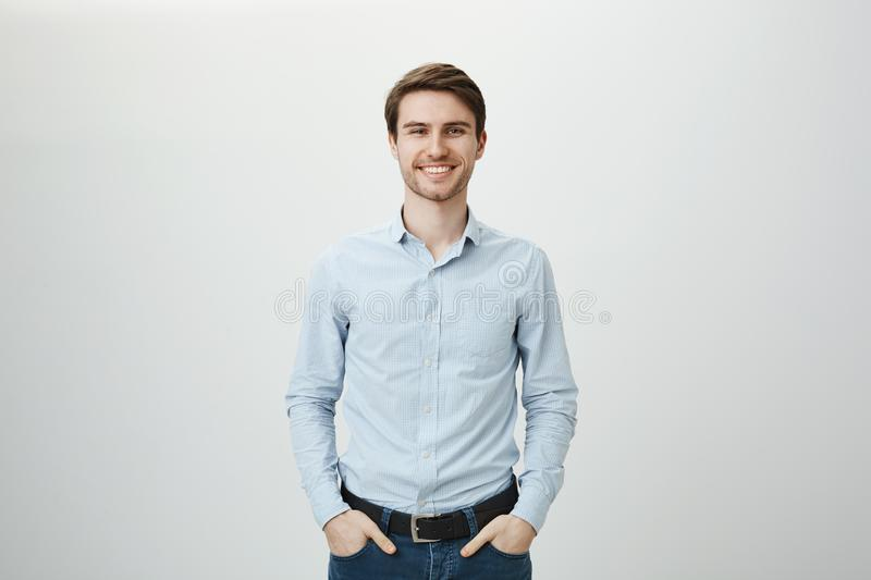 Confidence and business concept. Portrait of charming successful young entrepreneur in blue-collar shirt, smiling stock photo