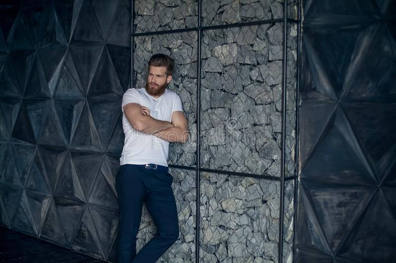 Confidence and charisma. Attractive young man keeping arms crossed and looking away while standing against modern grey background stock image
