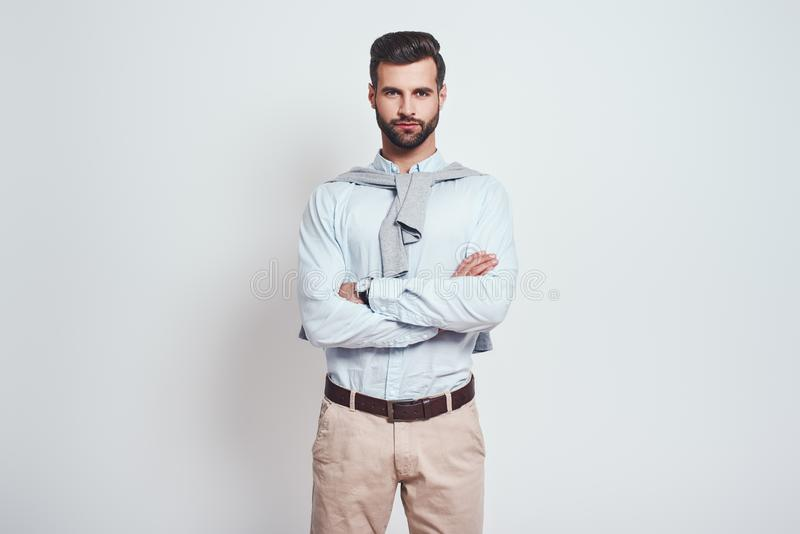 Confidence. Charming bearded man with crossed arms is looking at camera while standing on a grey background stock images