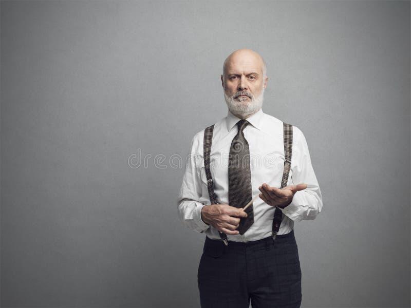 Confident academic professor posing and holding a stick. Confident serious academic professor posing and holding a stick stock photography