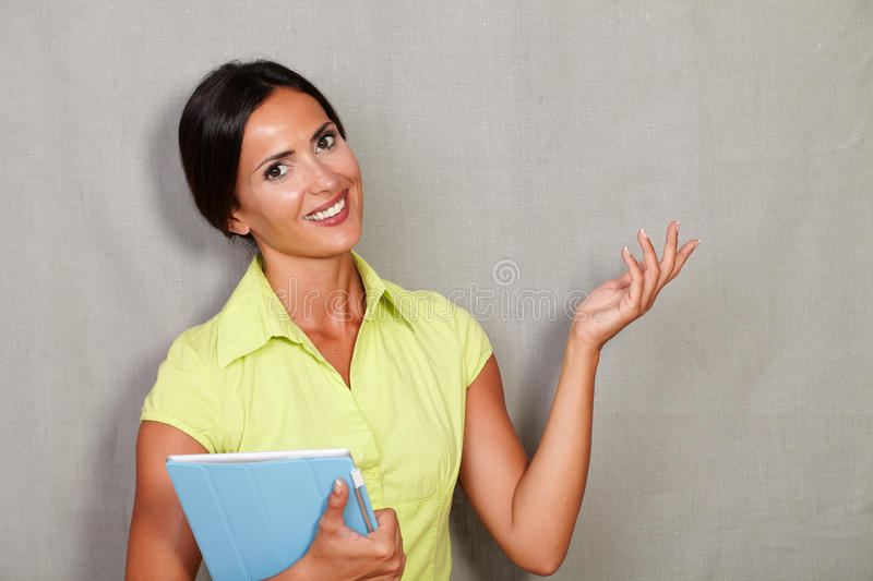 Confident adult woman carrying a tablet royalty free stock image