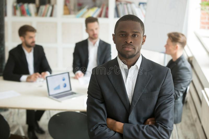 African american worker posing to camera at company briefing. Confident african american businessman looking at camera, work team negotiating behind. Black group royalty free stock image