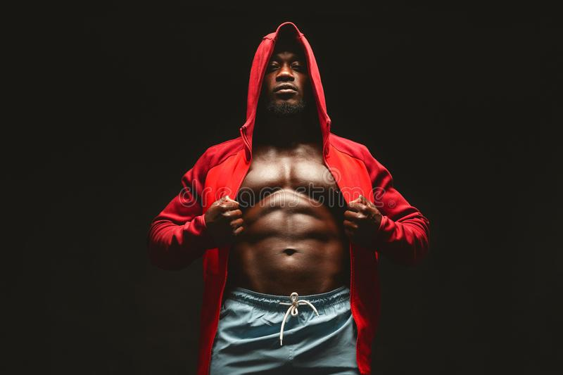 Confident african bodybuilder in red hooded shirt with bare chest. Black studio background royalty free stock photography