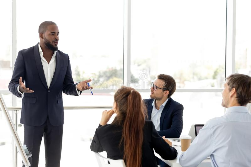 African business coach in suit giving presentation to clients. Confident african boss giving presentation to company clients, trainer presenting new project royalty free stock photography
