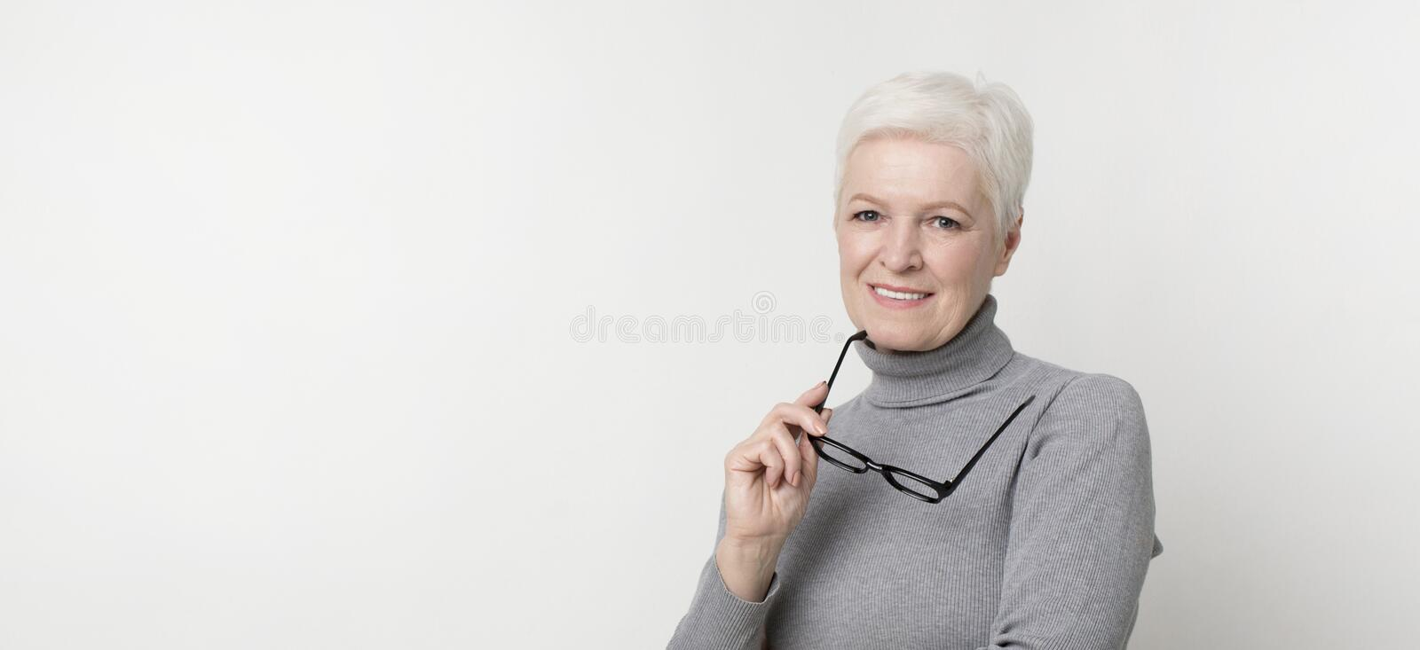 Confident aged businesswoman holding glasses looking at camera royalty free stock photography