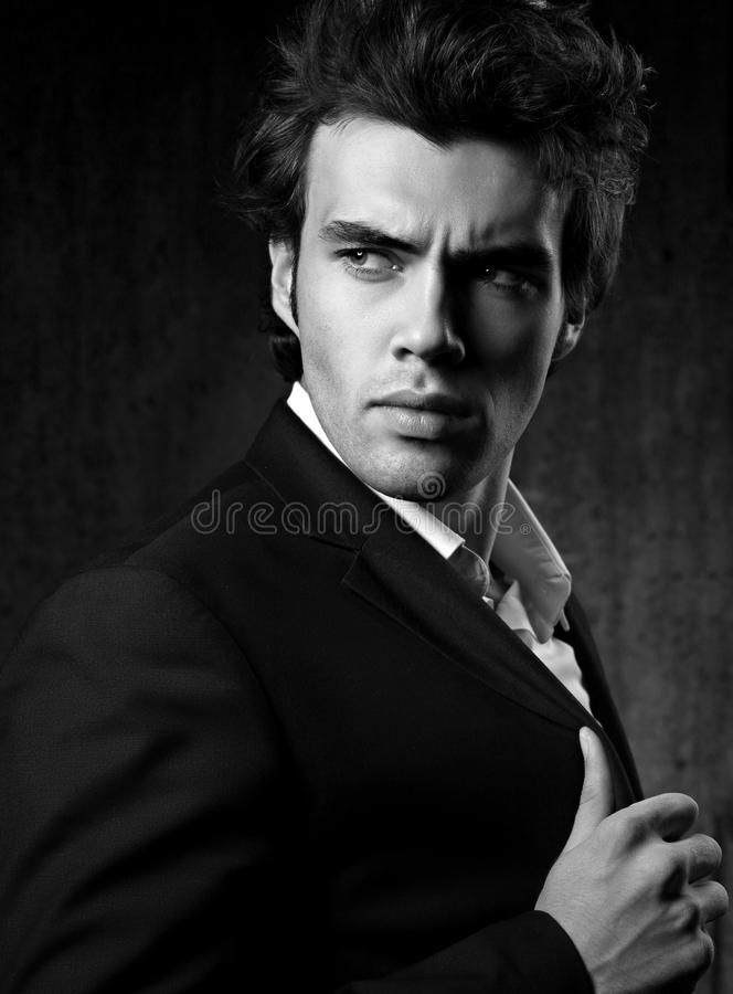 Confident ambitious handsome man with strained look posing in fa. Shion suit and white style shirt on dark shadow background. Closeup black and white portrait stock photo