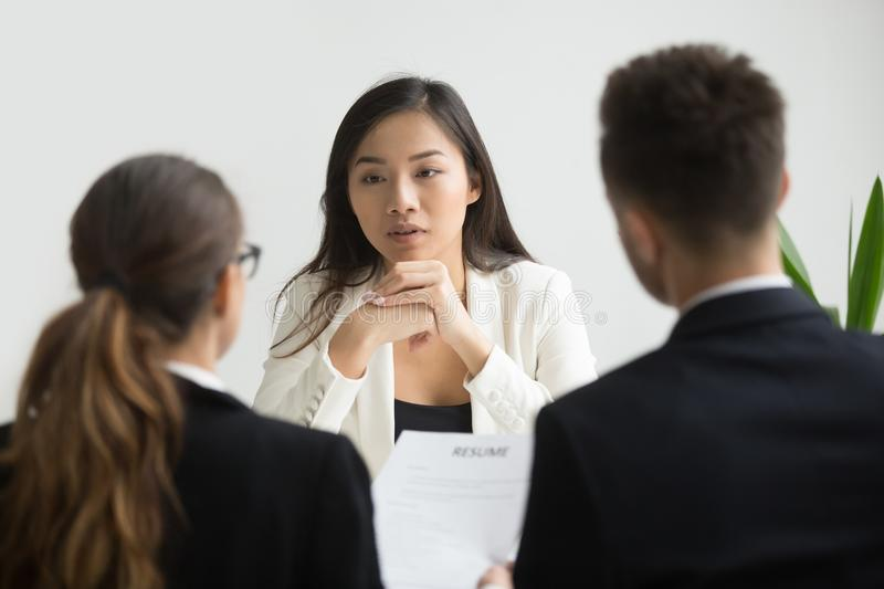 Confident applicant smiling at job interview with diverse hr man. Confident asian female applicant convincing hr managers to hire her at job interview, young royalty free stock image