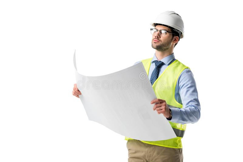 Confident architect in glasses wearing reflective vest and hardhat looking at blueprint stock image