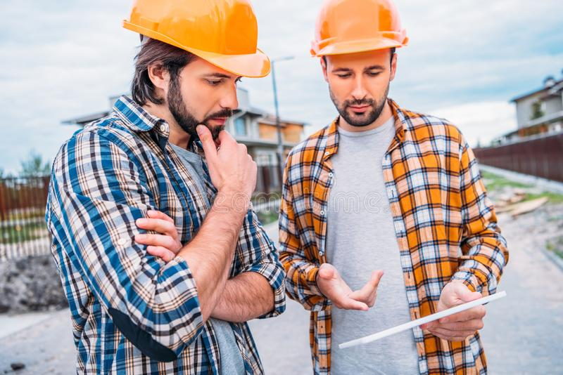 Confident architects using digital tablet. At construction site stock photography