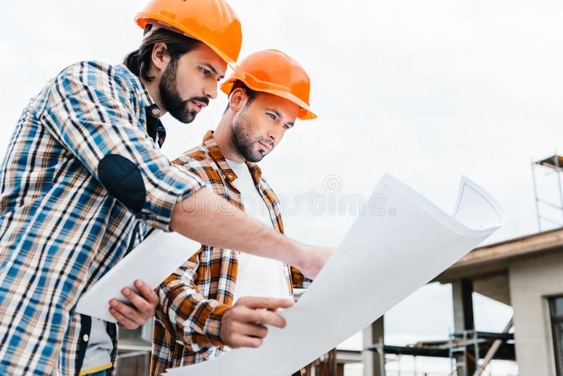 Confident architects working together. With construction plan royalty free stock photography