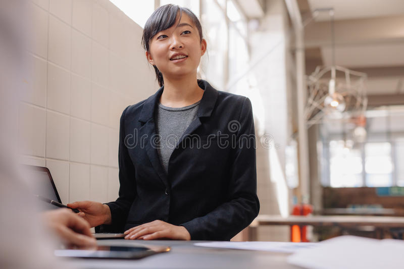 Confident asian business woman giving presentation. Shot of confident young asian business woman giving presentation to coworkers in office stock photos