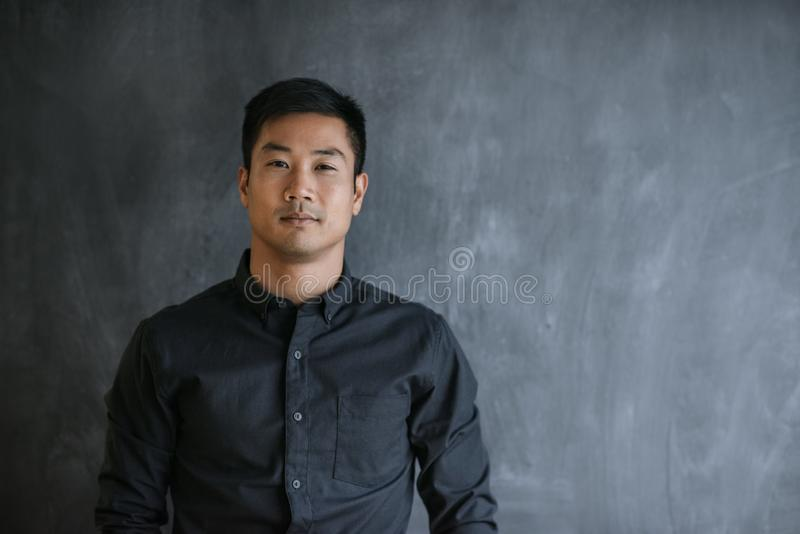 Confident Asian businessman standing in front of a blank chalkboard royalty free stock image