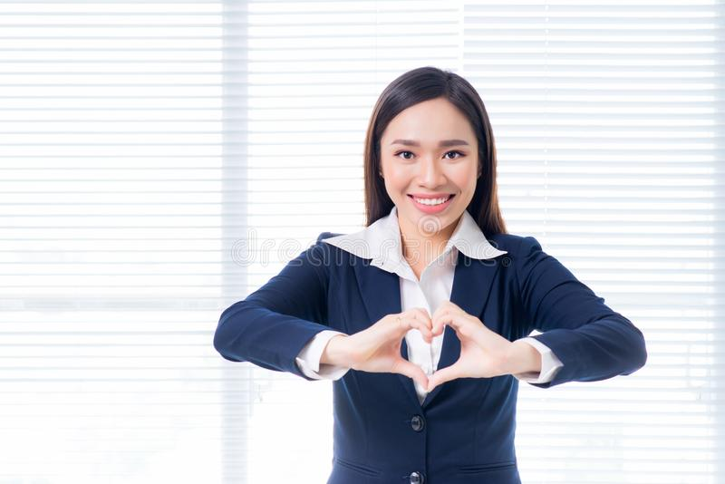 Confident asian businesswoman gesture hands making heart shape.  royalty free stock image