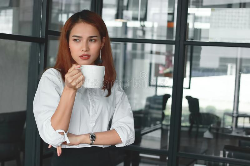 Confident Asian businesswoman standing and holding coffee cup in office. Leader business woman concept. Confident Asian businesswoman standing and holding royalty free stock images