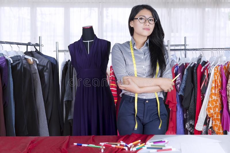 Confident Asian fashion designer keeping arms crossed royalty free stock image