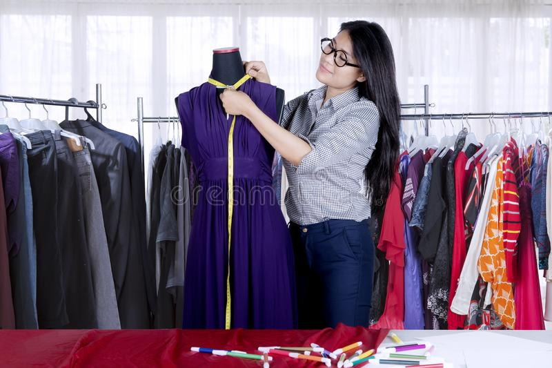 Confident Asian fashion designer measuring garment on dressmaker`s model royalty free stock photo