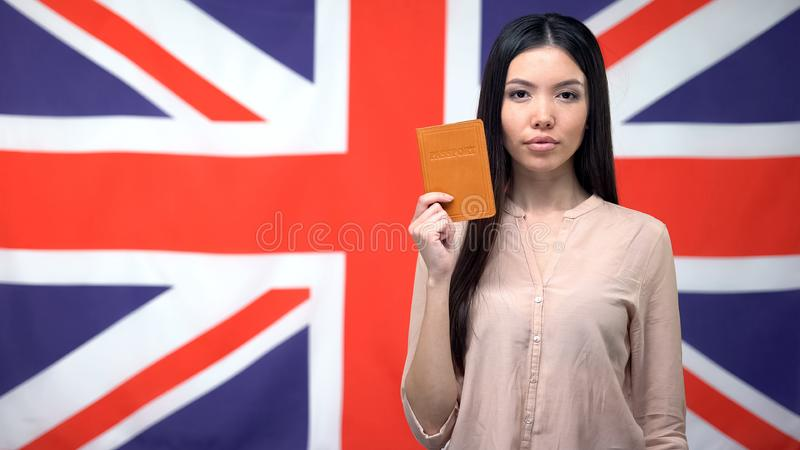 Confident Asian woman showing passport against British flag background, emigrant stock photo