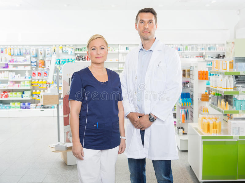 Confident Assistant And Pharmacist Standing In Pharmacy royalty free stock image