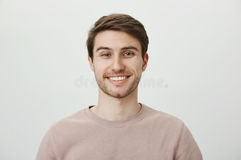 Confident attractive caucasian guy in beige pullover smiling broadly while standing against gray background, feeling. Self-assured while helping out customer stock images