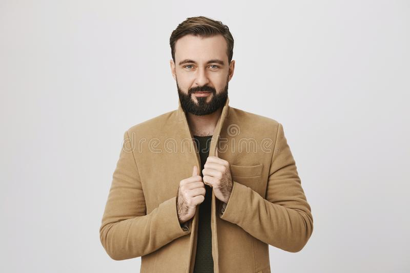 Confident attractive mature man with beard, holding hands on his coat, looking at camera while standing over gray stock photography