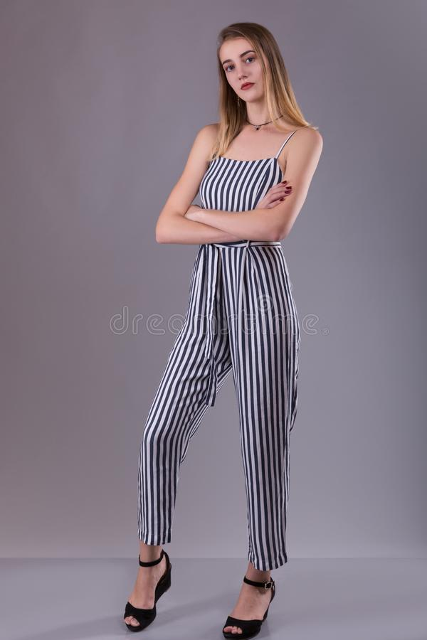 Confident attractive slender young woman wearing striped overall standing with folded arms looking thoughtfully at the camera over stock photography