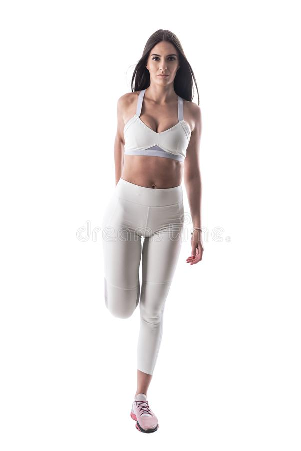 Confident attractive sporty woman in white yoga pants stretching leg muscles looking at camera. royalty free stock photography