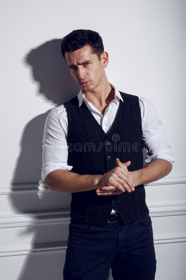 Confident, attractive young man in elegant clothes near white wall, posing in studio, lights of studio. Young handsome man wearing white shirt, black vest stock image