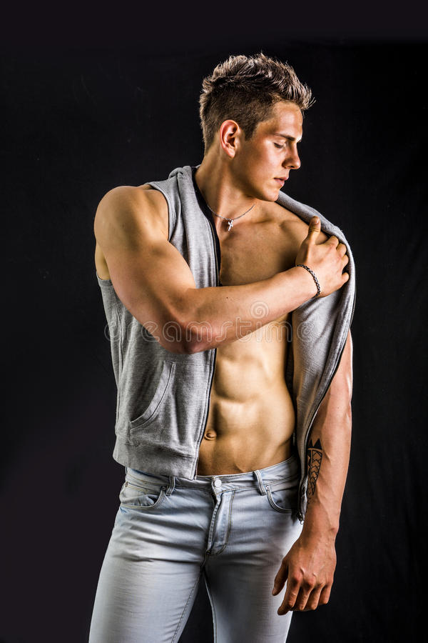 Confident, attractive young man with open vest on