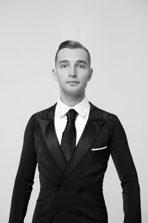 Confident attractive young man in tuxedo. Portrait of Confident attractive handsome ballroom dancer young man in tuxedo isolated on grey background stock photography