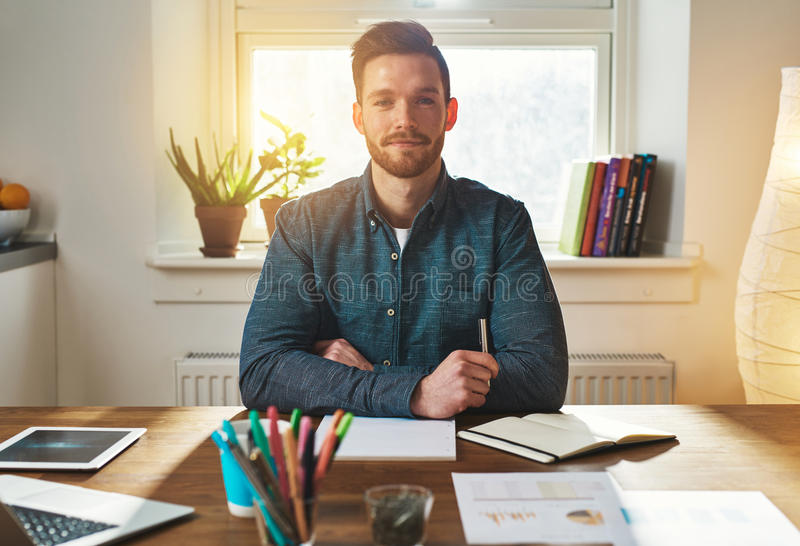 Confident authoritative young businessman. Working from a home office sitting looking at the camera with a thoughtful proud expression royalty free stock photography