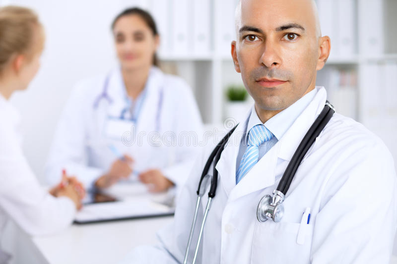 Confident bald doctor man with medical staff at the hospital royalty free stock image