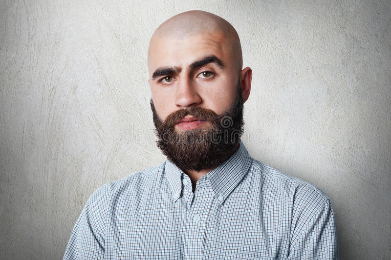 A confident bald male with thick black eyebrows and beard wearing checked shirt having gloomy expression posing against white back royalty free stock photos