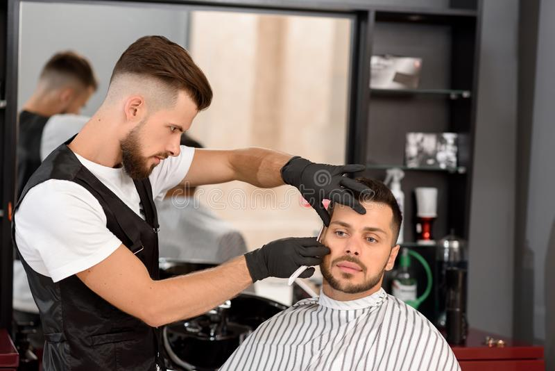 Confident barber shaving client`s beard with sharp razor. royalty free stock images