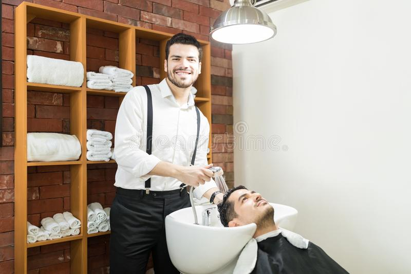 Barber Smiling While Washing Customer`s Hair With Shower stock photography
