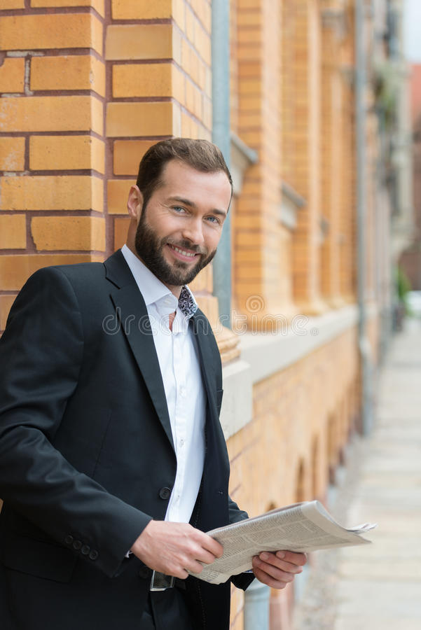 Confident bearded businessman with a newspaper royalty free stock photos