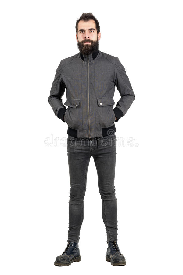 Confident bearded hipster in gray jacket, tight jeans and army boots looking at camera. Full body length portrait isolated over white studio background royalty free stock image