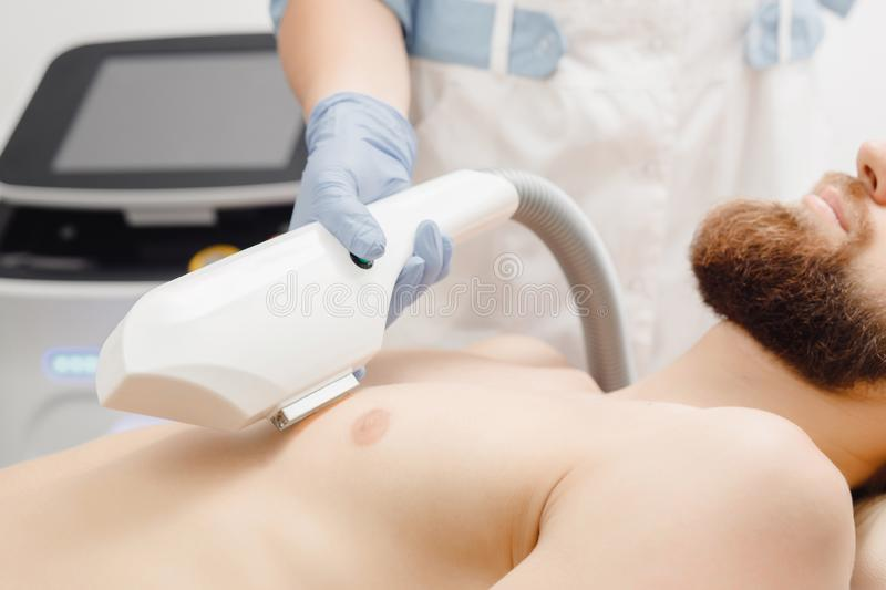Male procedure to remove hair from breast with help of special laser equipment. Concept beauty and health stock photos