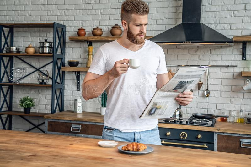 Confident bearded man is taking a rest standing in the kitchen in the morning eating croissant with coffee, reading morning press stock images