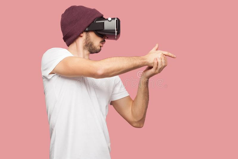 Confident bearded young hipster man in white shirt and casual hat standing, wearing vr playing video game, showing gun sing with stock image